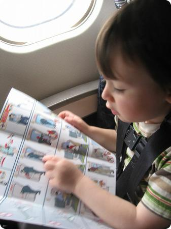 Toddler reading the Airplane Safety Manual