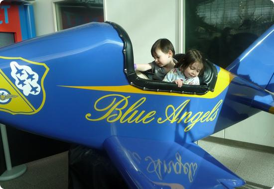 Everest and Darya pretend to be Blue Angels Pilots at Seattle's Boeing Museum of Flight