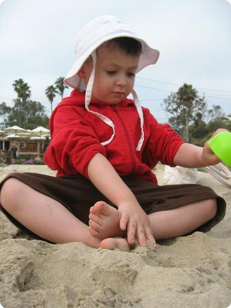 E explores the sand at Crystal Cove in Laguna Beach, CA
