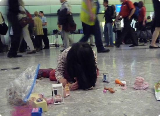 Darya spreads out her toys and plays in Heathrow's Baggage Claim Area