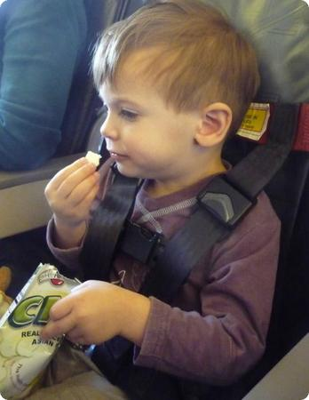 Eilan sits safely in his own airplane seat using the CARES harness