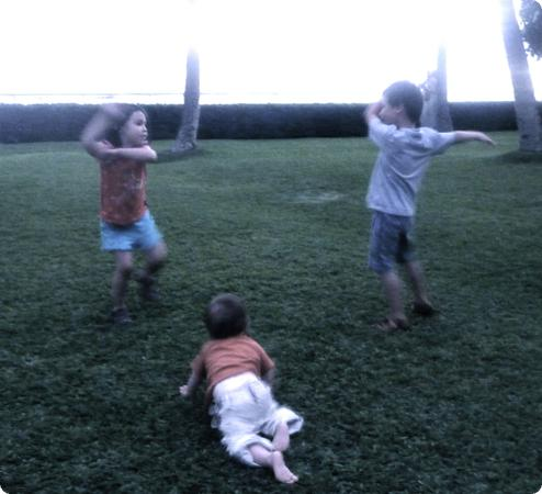 Eilan, Everest and Darya practice their hula moves on a lawn overlooking Waikiki Beach