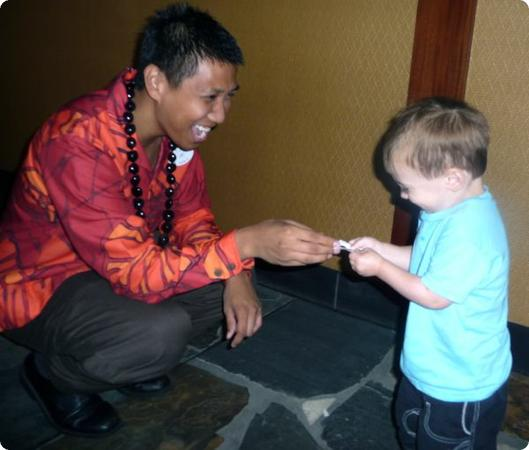 A cast member takes a moment to hand Eilan a Mickey Mouse sticker