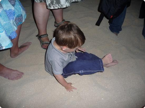 Eilan plays in the sand, oblivious to the crowds massed around him