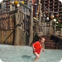 Eilan runs through the shallow water under the Menehune Bridge at Aulani Resort