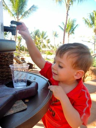 Eilan helps himself to a cup of water at a poolside water station at Aulani Resort