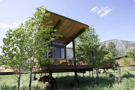 Each hut's balcon looks out over a grassy meadow