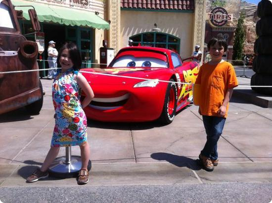 Darya and Everest pose in front of Lightning McQueen at Carsland